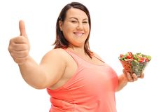 Overweight woman with a salad bowl making a thumb up sign Stock Image