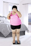 Overweight woman with scale in the bedroom royalty free stock photography