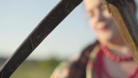 Overweight woman sharpening scythe preparing to start mow on the green summer field. Farmer sharpening the scythe with a. Portrait of beautiful Slavic overweight stock footage