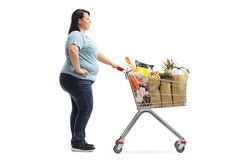 Overweight woman with a shopping cart waiting in line Stock Photo