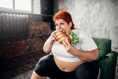 Overweight woman eats sandwich, bulimic. Overweight woman sits in a chair and eats sandwich, bulimic. Unhealthy lifestyle, obesity royalty free stock photography