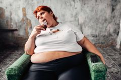 Overweight woman sits in chair and eats sweet cake. Overweight woman sits in a chair and eats sweet cake, laziness and obesity, bulimic. Unhealthy food eating Stock Photos
