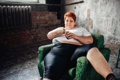 Overweight woman sits in a chair and eats sweets. Unhealthy lifestyle, obesity Stock Photography