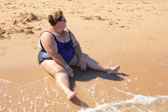 Overweight woman sitting on beach Stock Images