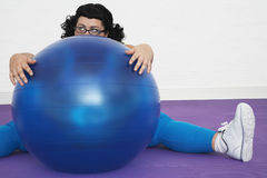 Overweight Woman Sitting Behind Exercise Ball Stock Image