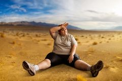 Overweight woman sitting in desert valley. Burning of calories. Female obesity, bulimic. Unhealthy food eating Royalty Free Stock Photo