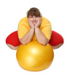 Overweight woman sitting with gym ball Royalty Free Stock Images