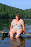 Overweight woman sitting on stage royalty free stock photography