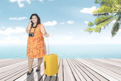 Overweight woman with smartphone on the jetty. Image of overweight woman talking on a mobile phone while standing with a suitcase on the jetty Stock Photo