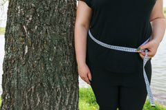 Overweight woman stand wrapped with measure tape stock image
