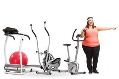 Overweight woman standing by exercise machines and pointing. Full length portrait of an overweight woman standing by exercise machines and pointing isolated on Royalty Free Stock Photography