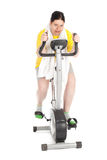Overweight woman on stationary fitness bicycle Royalty Free Stock Photo