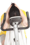 Overweight woman on stationary fitness bicycle Stock Photo