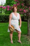 Overweight woman with a straw hat. Forty something brunette woman wearing a sun dress holding straw hat Royalty Free Stock Photo