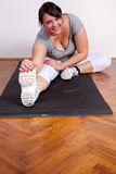 Overweight woman stretching Royalty Free Stock Photo