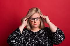 An overweight woman in studio, touching temples with her hands because of headache. stock image