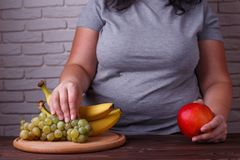 Overweight woman taking some grapes from the dish. Dieting, usef. Ul sweets, low calorie food Royalty Free Stock Photography