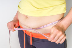 Overweight woman with tape is measuring fat on belly Royalty Free Stock Photos