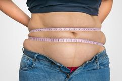 Overweight woman with tape is measuring fat on belly stock photos