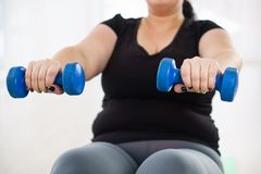 Overweight woman training with dumbbells. Interval workout, power fitness, activity, healthy lifestyle, sport, weight loss, tabata overweight woman training with stock images