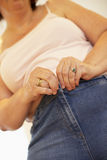 Overweight Woman Trying To Fasten Trousers Stock Photography