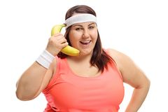 Overweight woman using a banana as a telephone Stock Photos