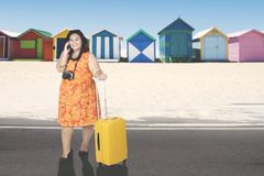 Overweight woman with smartphone in the cottage. Overweight woman using a mobile phone while standing with a suitcase in the beach cottage Stock Photography