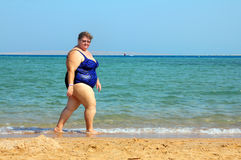 Overweight woman walking on beach Stock Photos