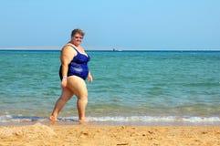 Overweight woman walking on beach Stock Photos