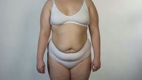 Overweight woman wearing undies posing for camera, obesity, unhealthy nutrition. Stock photo royalty free stock photography