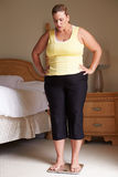 Overweight Woman Weighing Herself On Scales In Bedroom royalty free stock images