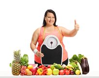 Overweight woman with a weight scale making a thumb up gesture b Stock Photography