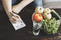 Overweight woman writing diet plan into copy book stock photos