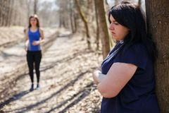 Overweight woman depressed and unsatisfied, no motivation for tr. Overweight women depressed and unsatisfied, no motivation for training. Laziness Royalty Free Stock Image