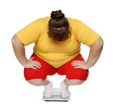 Overweight women on scales. Overweight women sitting on scales isolated on white Royalty Free Stock Photos