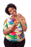 Overweight young black woman drinking orange juice - African peo Stock Image