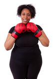 Overweight young black woman holding boxing gloves - African peo Royalty Free Stock Photography