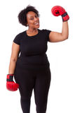 Overweight young black woman holding boxing gloves - African peo Royalty Free Stock Photos