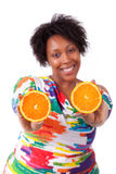 Overweight young black woman holding  orange slices - African pe Stock Images