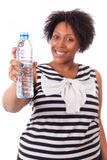 Overweight young black woman holding an water bottle - African p. Overweight young black woman holding an water bottle, isolated on white background - African Royalty Free Stock Photo