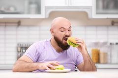 Overweight young man with unhealthy food at table. In kitchen Stock Image