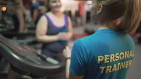 Overweight young woman asking personal training for advice on exercises in gym. Stock footage stock footage