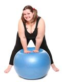 Overweight young woman with blue ball. Royalty Free Stock Images