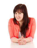 Overweight young woman leaning on table, smiling Royalty Free Stock Photos