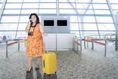 Overweight woman in the airport terminal. Overweight young woman speaking on a mobile phone while standing with a baggage in the airport terminal Royalty Free Stock Photos