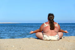 Overweightl woman meditation on beach royalty free stock photography