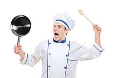 Overweldigd de keukenwerktuig van de chef-kokholding Stock Fotografie