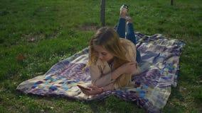 Overweldigend de tekstoverseinen van het blondemeisje op mobiele telefoon stock footage