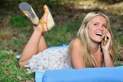 Overweldigend jonge blondevrouw in sundress die - op celtelefoon spreken Royalty-vrije Stock Afbeeldingen