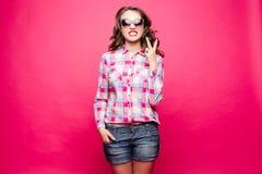 Overweldigend meisje in borrels en overhemd die zonnebril dragen die vredesteken tonen royalty-vrije stock foto
